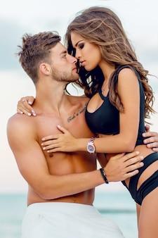 Retrato de moda de cerca al aire libre de una pareja muy sexy enamorada abrazos en la increíble playa tropical, vistiendo elegantes trajes de baño