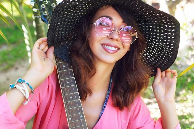 Retrato de moda de chica hermosa con maquillaje natural y pelos morenos mullidos posando en el jardín con guitarra. con sombrero y gafas de sol rosas redondas de moda.