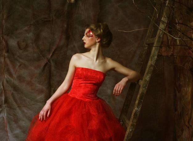 Retrato de moda de chica hermosa romántica con peinado, labios rojos, vestido de arte