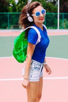 Retrato de moda de cierre al aire libre de mujer deportiva bronceada sensual feliz posando en el suelo