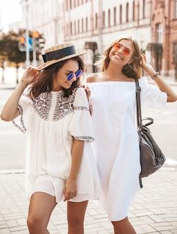 Retrato de moda de dos jóvenes hippie con estilo morena y rubia mujer en día soleado de verano. modelos vestidos con ropa blanca hipster. mujer posando. volviéndose loco