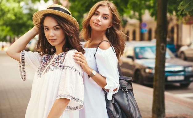 Retrato de moda de dos jóvenes hippie con estilo morena y rubia mujeres modelos en día soleado de verano en ropa hipster blanco posando. sin maquillaje