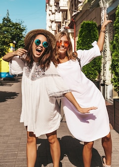 Retrato de moda de dos jóvenes hippie con estilo morena y rubia mujeres modelos en día soleado de verano en ropa hipster blanco posando