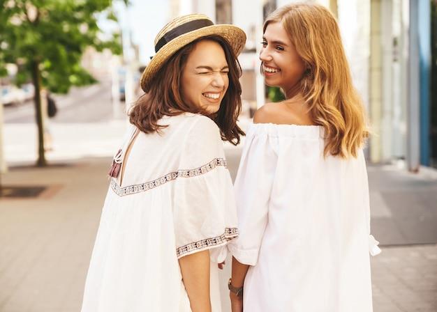 Retrato de moda de dos jóvenes hippie con estilo morena y rubia mujeres modelos sin maquillaje en día soleado de verano en ropa hipster blanco posando. giro de vuelta