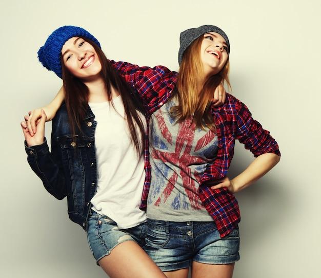 Retrato de moda de dos mejores amigas elegantes sexy hipster, con sombreros y trajes de botín lindo. sobre fondo gris.
