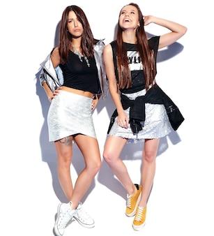 Retrato de moda de dos modelos morenas sonrientes en ropa casual de verano hipster aislado en blanco. longitud total