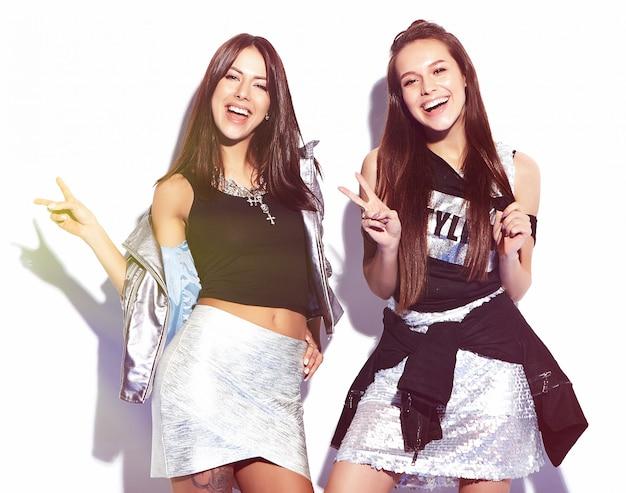 Retrato de moda de dos modelos morenas sonrientes en ropa casual de verano hipster aislado en blanco
