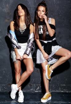 Retrato de moda de dos modelos de morenas sonrientes en ropa casual de verano negro hipster posando cerca de la pared gris oscuro