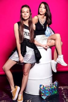 Retrato de moda de dos modelos de morenas sonrientes en verano ropa casual casual negro posando en rosa, sentado en barril blanco