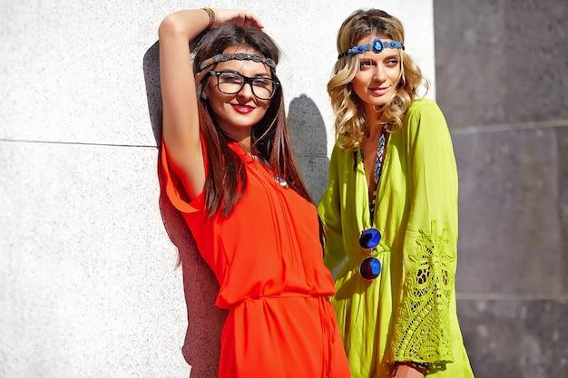 Retrato de moda de dos modelos de mujeres jóvenes hippie en día soleado de verano en ropa hipster colorido brillante