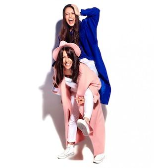 Retrato de moda de dos modelos de mujeres morenas sonrientes en verano casual hipster abrigo aislado en blanco. chicas abrazándose en la espalda