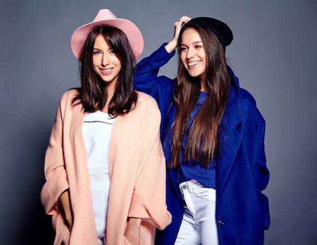 Retrato de moda de dos modelos de mujeres morenas sonrientes en verano casual hipster abrigo posando en gris