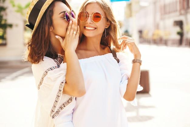 Retrato de moda de dos mujeres jóvenes con estilo hippie morena y rubia en día soleado de verano en ropa hipster blanco posando