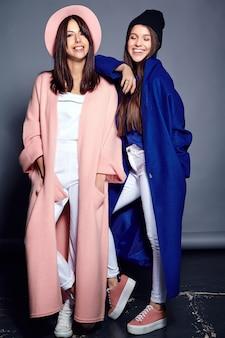 Retrato de moda de dos sonrientes modelos de mujeres morenas en abrigo casual hipster de verano posando en gris. longitud total