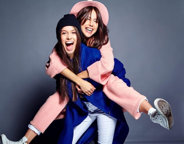 Retrato de moda de dos sonrientes modelos de mujeres morenas en verano casual hipster abrigo posando. chicas abrazándose en la espalda