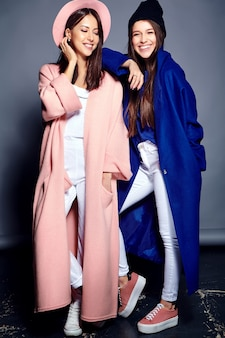 Retrato de moda de dos sonrientes modelos de mujeres morenas en verano casual hipster abrigo posando. longitud total