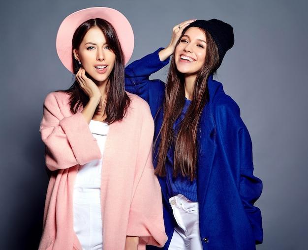 Retrato de moda de dos sonrientes modelos de mujeres morenas en verano casual hipster abrigo posando