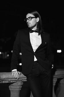 Retrato de moda elegante pelo largo joven. modelo masculino atractivo y guapo en traje negro con bigote en la calle por la noche