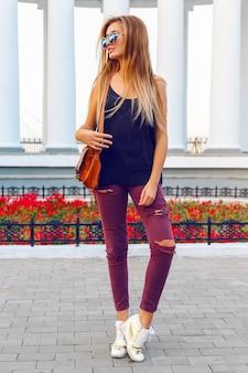 Retrato de moda de estilo callejero de joven mujer sexy en zapatillas de tacón de jeans locos, tiene pelos ombre rubio de moda.