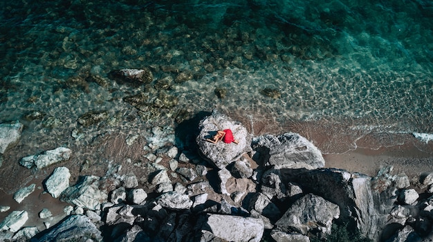 Retrato de moda de estilo de vida al aire libre de linda chica acostada en las grandes piedras en el mar vistiendo un elegante vestido rojo largo. solitario. arte fotografico. creativo. vista superior. estado de ánimo romántico