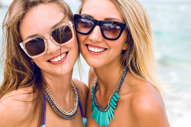 Retrato de moda de estilo de vida de dos bastante frescas jóvenes morenas y rubias mejores amigas chicas, que tienen vacaciones en la playa de la isla tropical, con gafas de sol bikini y joyas brillantes.