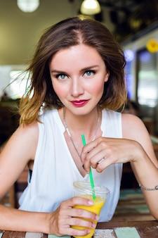 Retrato de moda de estilo de vida interior de mujer hermosa posando en el café, bebiendo jugo de mango sabroso saludable fresco, sonriendo, pasar un buen rato, maquillaje sexy brillante.