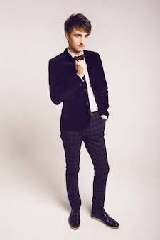 Retrato de moda de estudio de hombres guapos en elegante traje de lujo y pajarita, fondo claro, colores suaves.