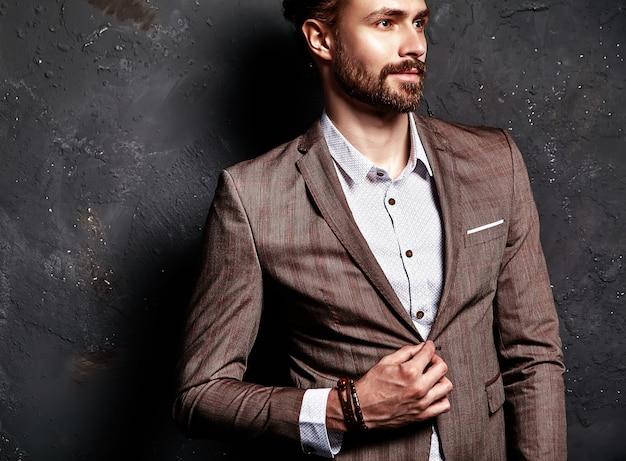 Retrato de moda guapo elegante empresario inconformista modelo vestido con elegante traje marrón cerca de la pared oscura