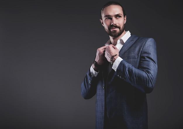 Retrato de moda guapo elegante hipster empresario modelo vestido con elegante traje azul posando en gris