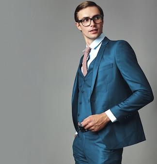 Retrato de moda guapo elegante hipster empresario modelo vestido con elegante traje azul posando sobre fondo gris en estudio en gafas