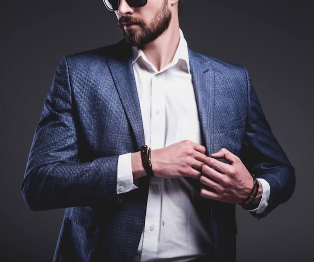 Retrato de moda guapo elegante hipster empresario modelo vestido con elegante traje azul sobre gris