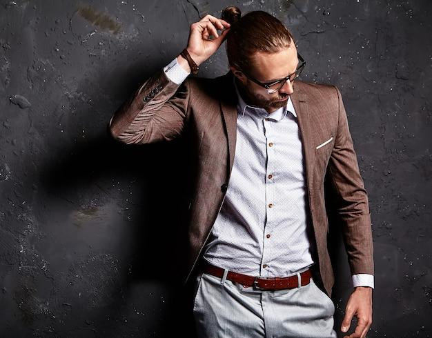 Retrato de moda guapo elegante hipster empresario modelo vestido con elegante traje marrón con gafas cerca de la pared oscura