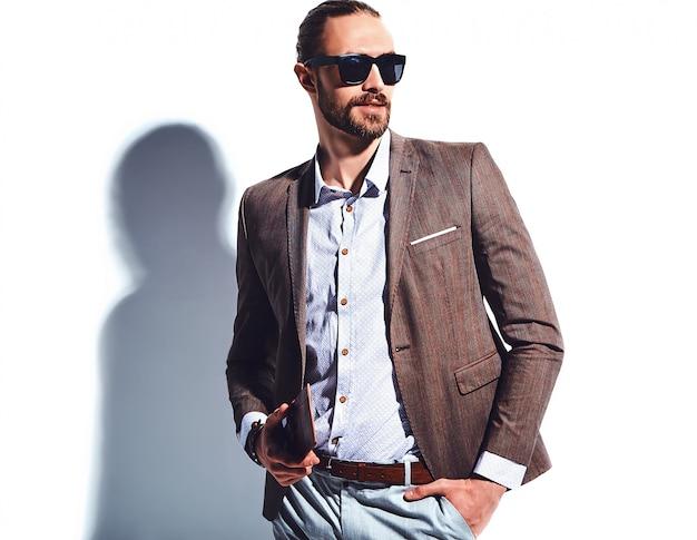 Retrato de moda guapo elegante hipster empresario modelo vestido con elegante traje marrón con gafas de sol