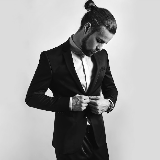Retrato de moda guapo elegante hipster empresario modelo vestido con elegante traje negro.