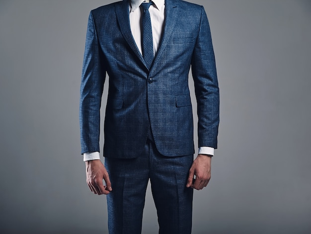Retrato de moda guapo empresario elegante modelo vestido con elegante traje azul posando sobre fondo gris en estudio