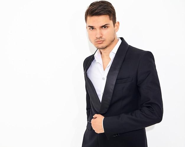 Retrato de moda guapo empresario elegante modelo vestido con elegante traje clásico negro posando. metrosexual
