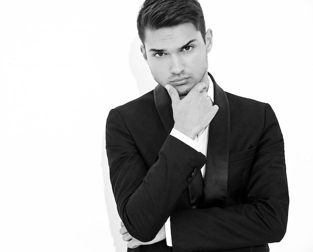 Retrato de moda guapo empresario elegante modelo vestido con elegante traje clásico negro. tocando su barbilla