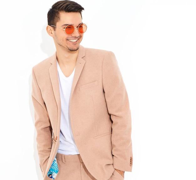 Retrato de moda guapo empresario elegante modelo vestido con elegante traje rosa claro posando. metrosexual