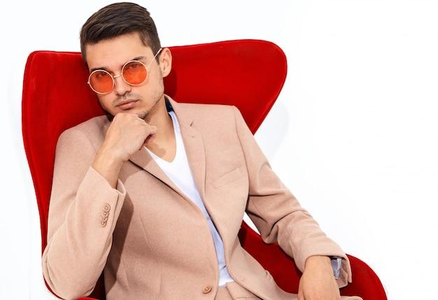Retrato de moda guapo empresario elegante modelo vestido con elegante traje rosa claro sentado en una silla roja. metrosexual