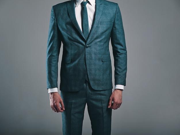 Retrato de moda guapo empresario elegante modelo vestido con elegante traje verde posando sobre fondo gris en estudio