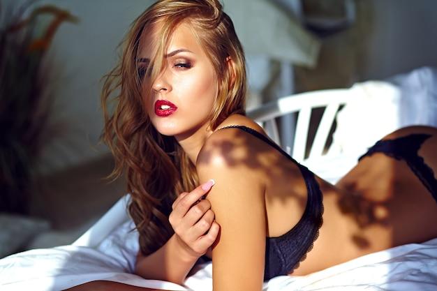 Retrato de moda de la hermosa modelo de mujer rubia adulta joven y sexy vistiendo lencería erótica negra acostada en la cama al atardecer