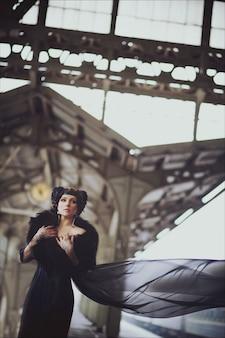 Retrato de moda de una hermosa morena con un vestido largo y mehndi en sus manos en el edificio de la antigua estación de tren. maquillaje creativo y peinado