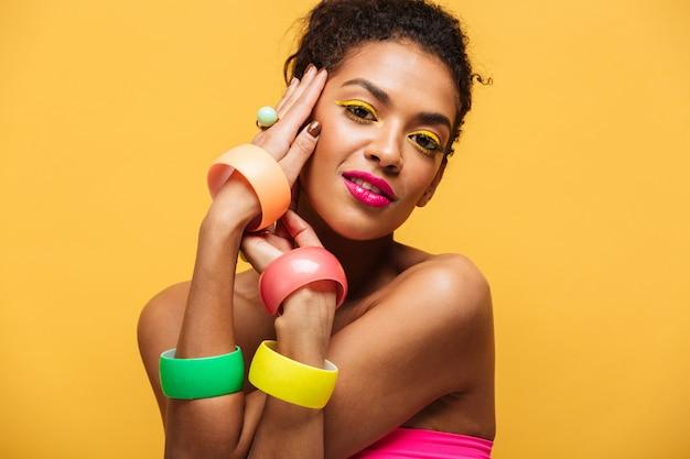 Retrato de moda de hermosa mujer afroamericana con maquillaje brillante demostrando joyas multicolores cogidos de la mano en la cara aislada, sobre amarillo