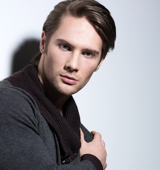 Retrato de moda de hombre joven sexy en poses casuales sobre pared con sombras de contraste