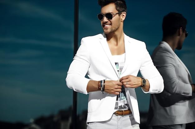Retrato de moda de hombre de negocios guapo joven modelo guapo hombre en traje casual de tela en gafas de sol en la calle