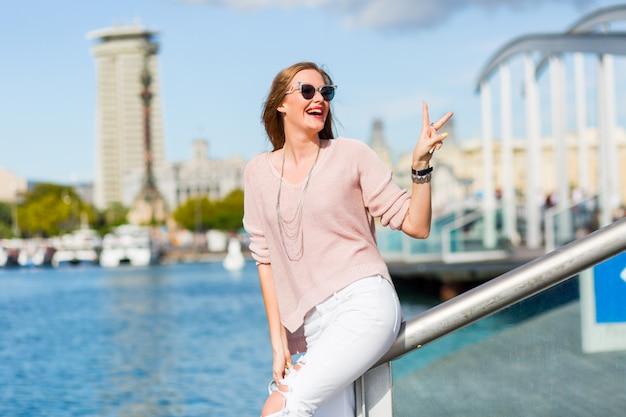 Retrato de moda de la increíble e increíble dama hipster en traje casual de primavera, joyas de moda, labios rojos disfrutando de las vacaciones en barcelona.