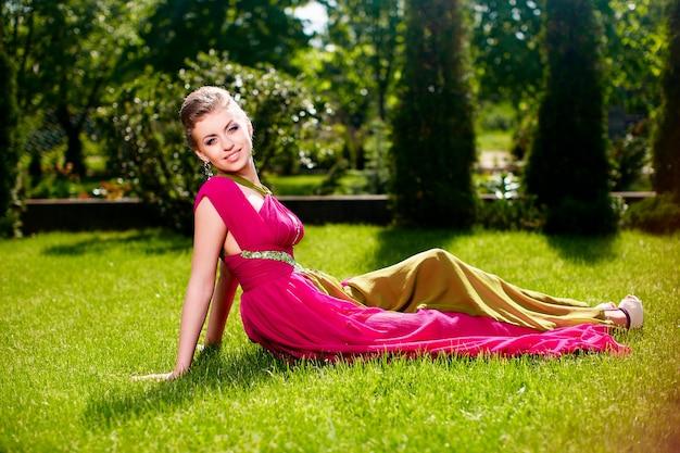 Retrato de moda de joven y bella mujer modelo dama mujer sonriente con peinado en vestido brillante posando al aire libre tumbado en la hierba verde