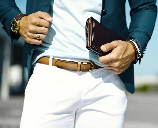 Retrato de moda de joven empresario guapo modelo hombre en traje de tela casual con accesorios en las manos