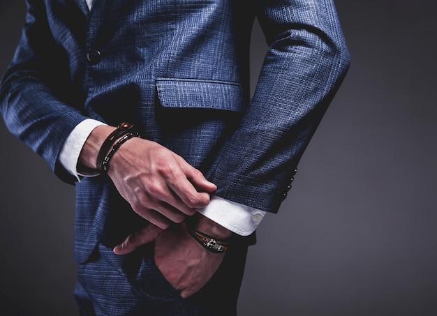 Retrato de moda de joven empresario guapo modelo hombre vestido con elegante traje azul sobre gris.
