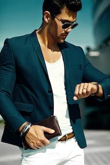 Retrato de moda de joven empresario sexy modelo guapo hombre en traje casual de tela en gafas de sol en la calle